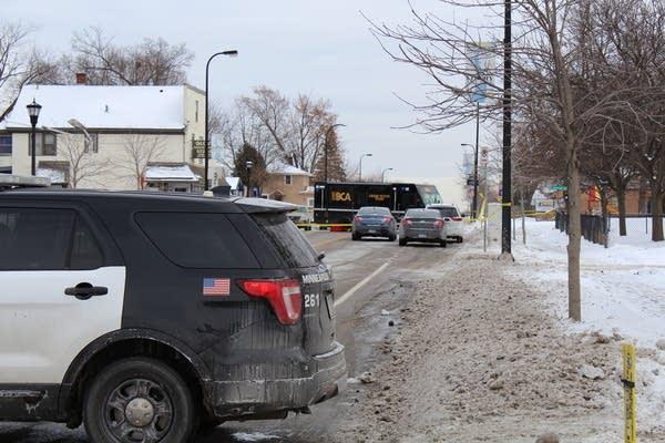 Vehicles sit along a snowy street