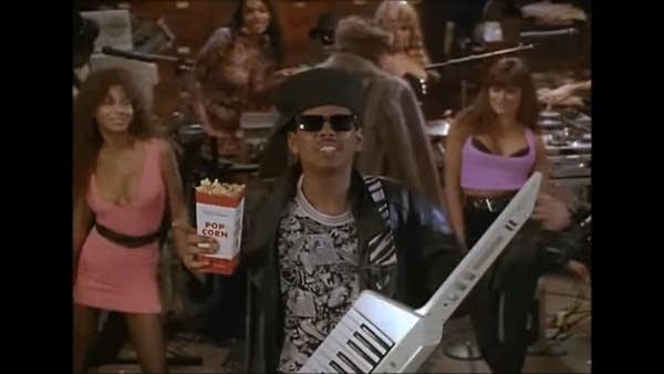 Musician Shock G w/ Keytar and box of popcorn w/ two women dancing