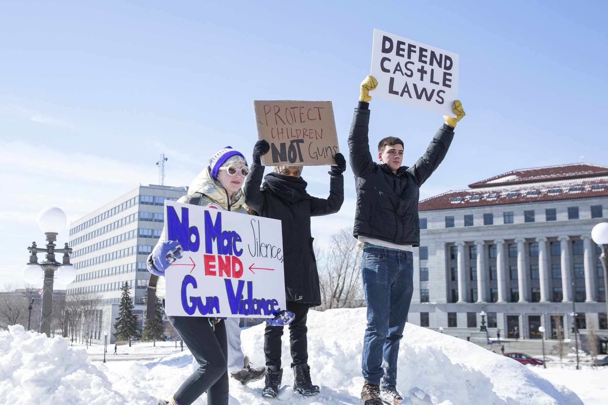 Students stand on a snow bank holding signs