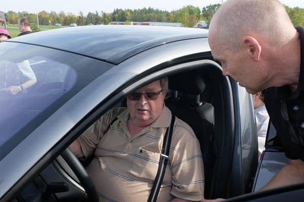 Two men talk through an open car door