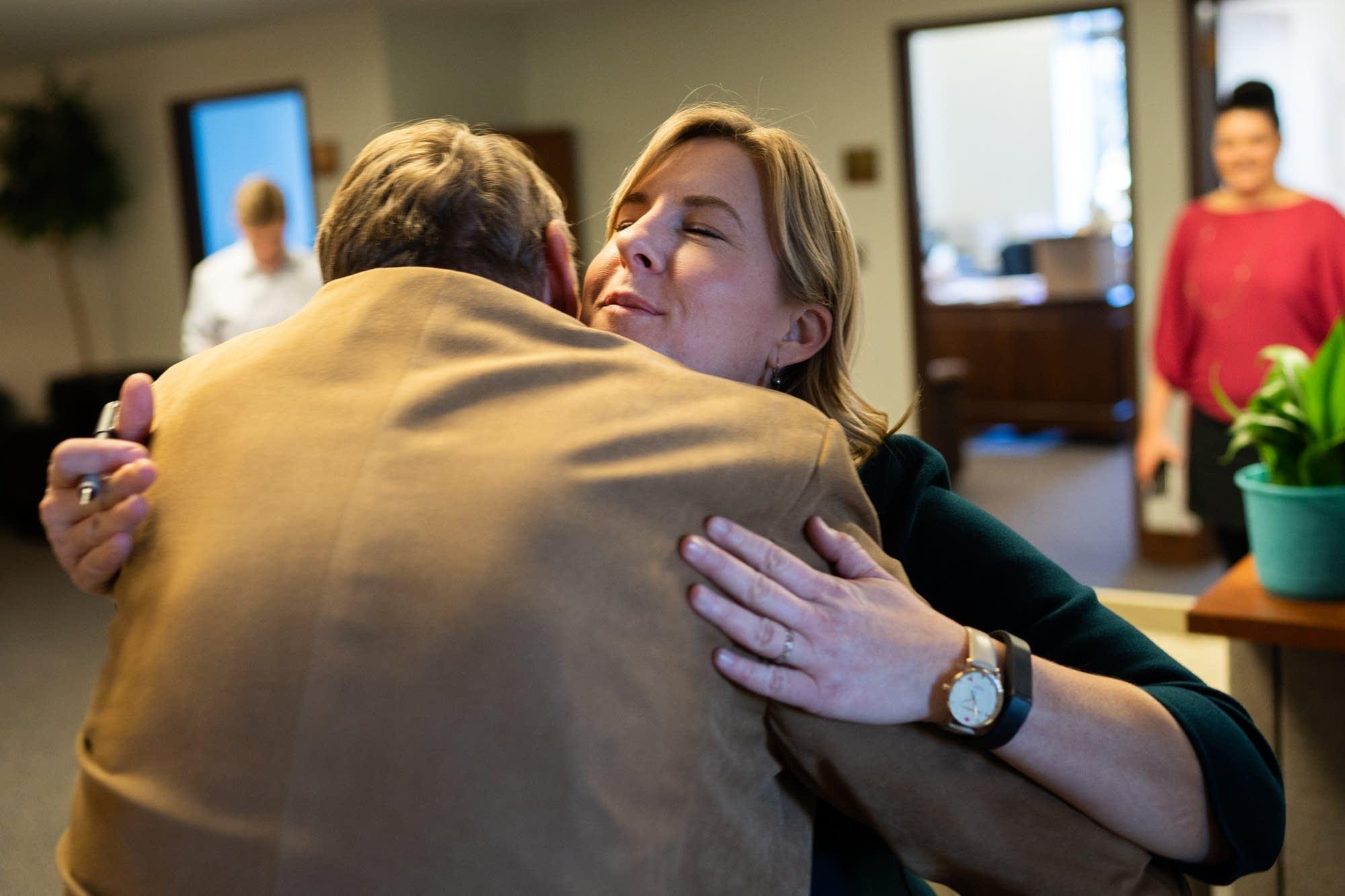 Rep. Melissa Hortman (DFL) hugs Rep. John Persell (DFL).