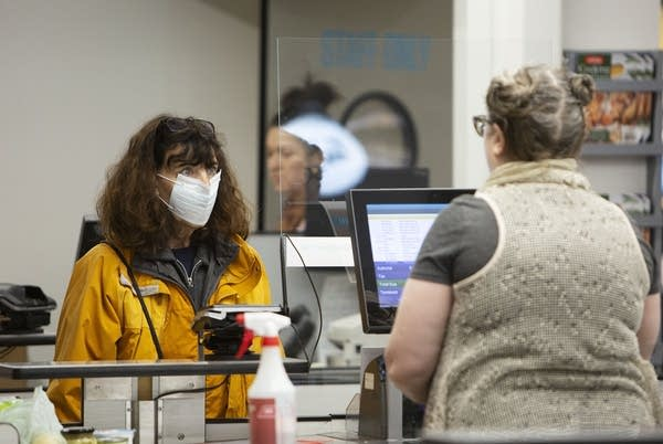 A woman wearing a mask at a checkout sign.