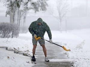 Peter Lidstone shovels his sidewalk during a storm