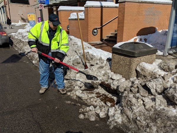 Greg Mizer shovels out a storm drain catch basin on Wabasha Street