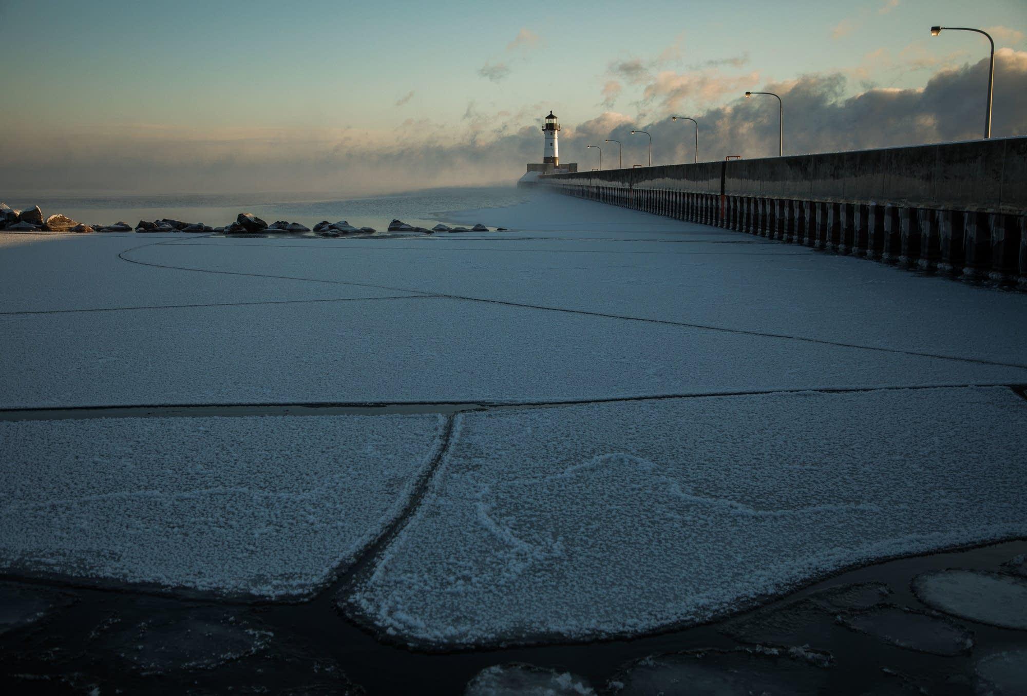 Pancake ice forms along the shoreline while sea smoke rises.