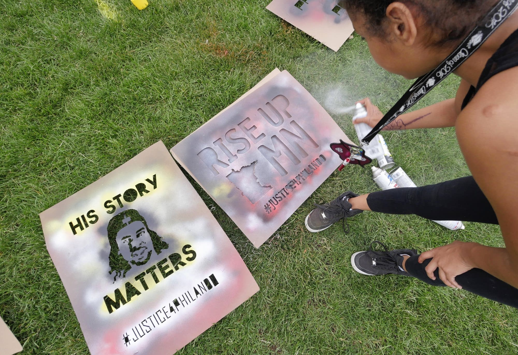 Ruthie Booker, 12, of Minneapolis paints signs.