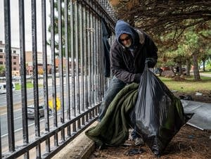 Marty Thomas packs blankets he hung to dry into a garbage bag.