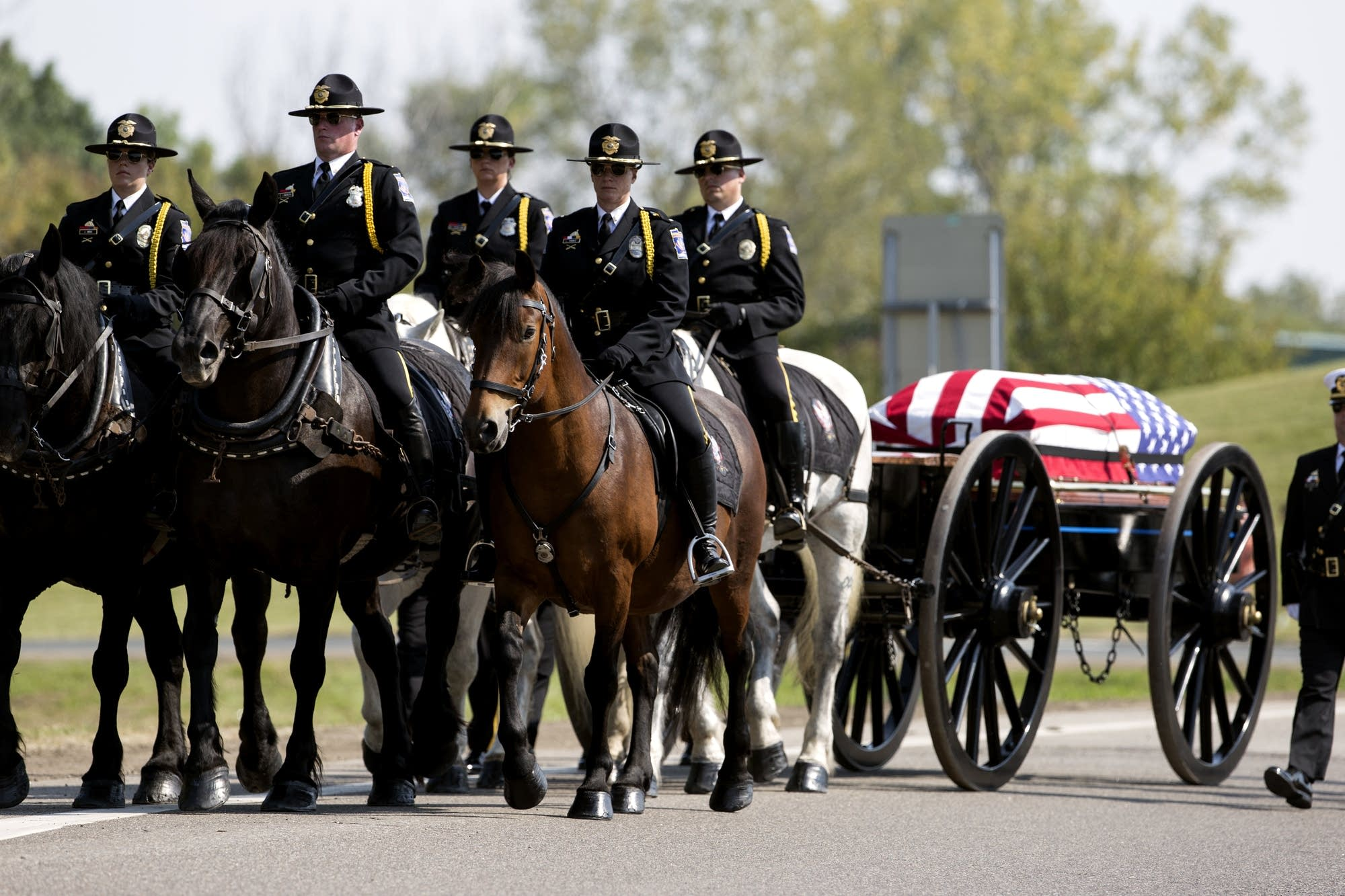 Officer Bill Mathews' casket is escorted to the grave site.