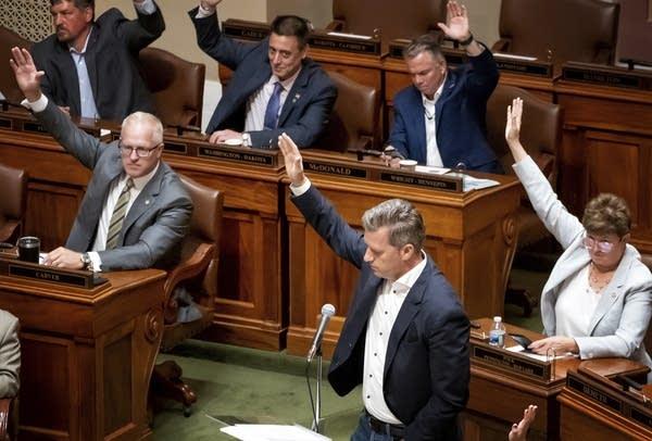 State legislators raise their hands to vote.