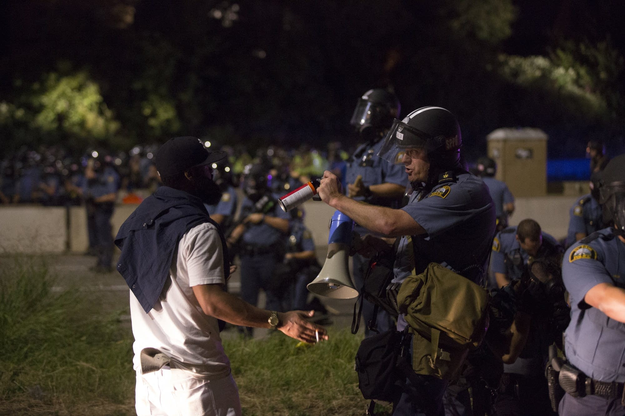 A protester faces off with police officer.