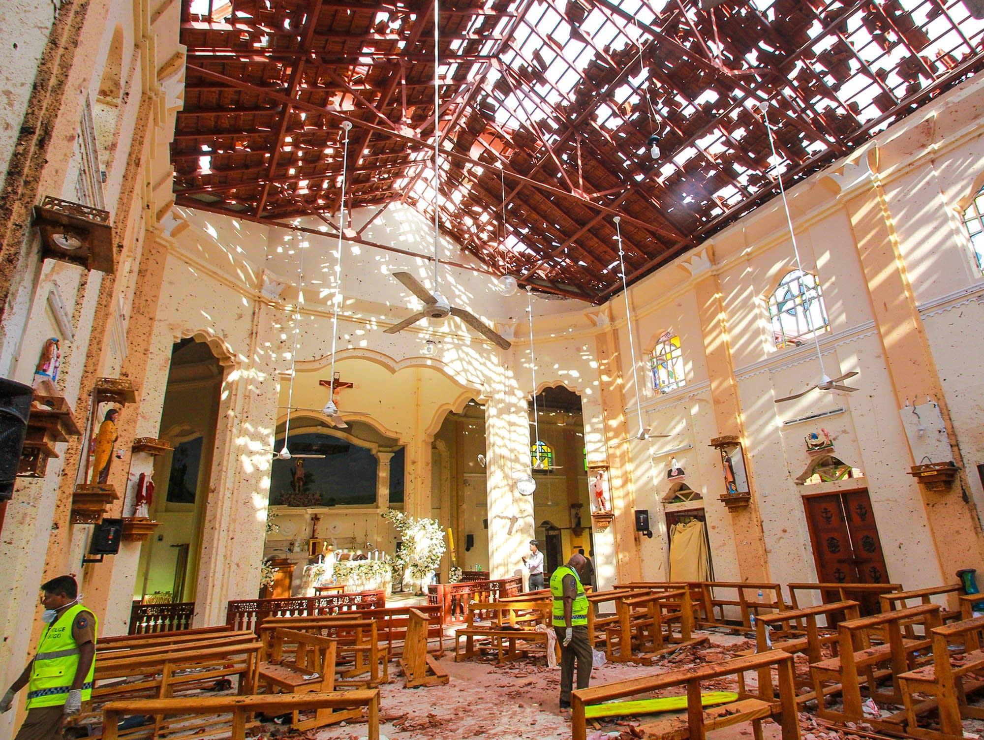 Sri Lankan officials inspect the damaged St. Sebastian's Church