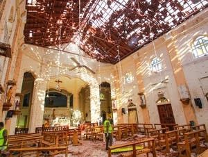Sri Lankan officials inspect the damaged St. Sebastian's Church
