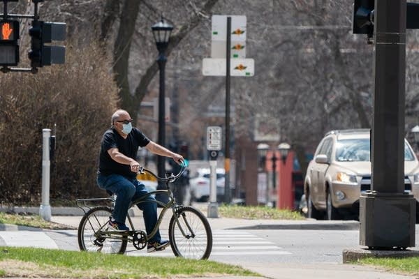 A man bikes with a mask on.