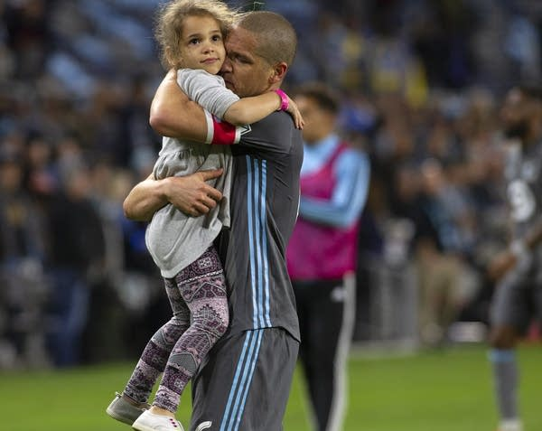 A soccer player hugs a young girl on the field