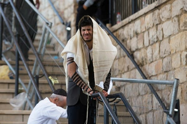A man prays on stairs.