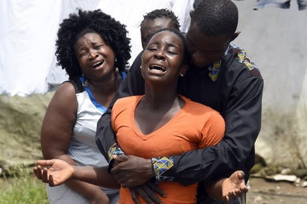 A woman reacts after her husband dies.