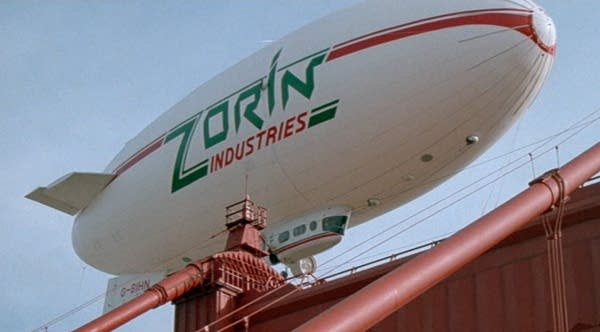 """White blimp, docked, that says """"ZORIN INDUSTRIES"""""""