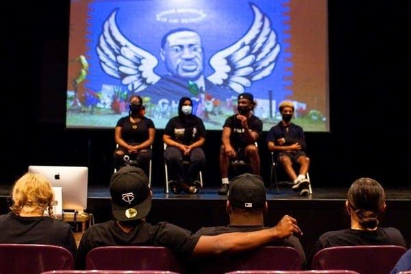 Students speak on stage.