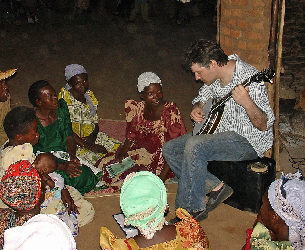 Bela performs banjo in Uganda