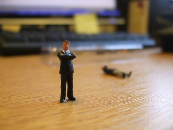 A small toy business man stands on a desk.