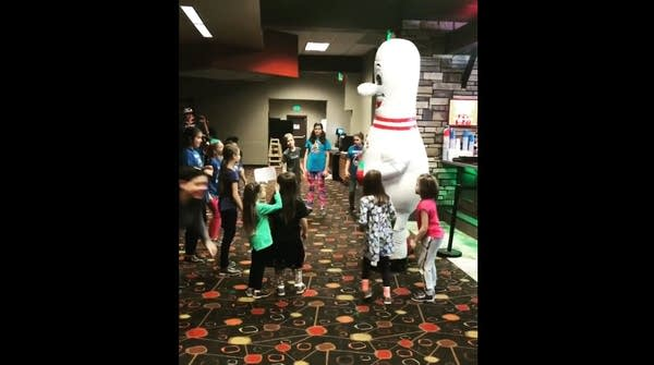 A bowling pin mascot surrounded by a entertained kids at bowling alley