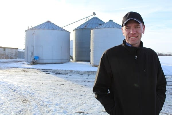 A man stands on in front of silos on a farm