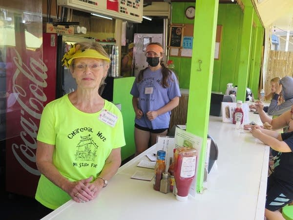 A woman stands at a state fair food stand