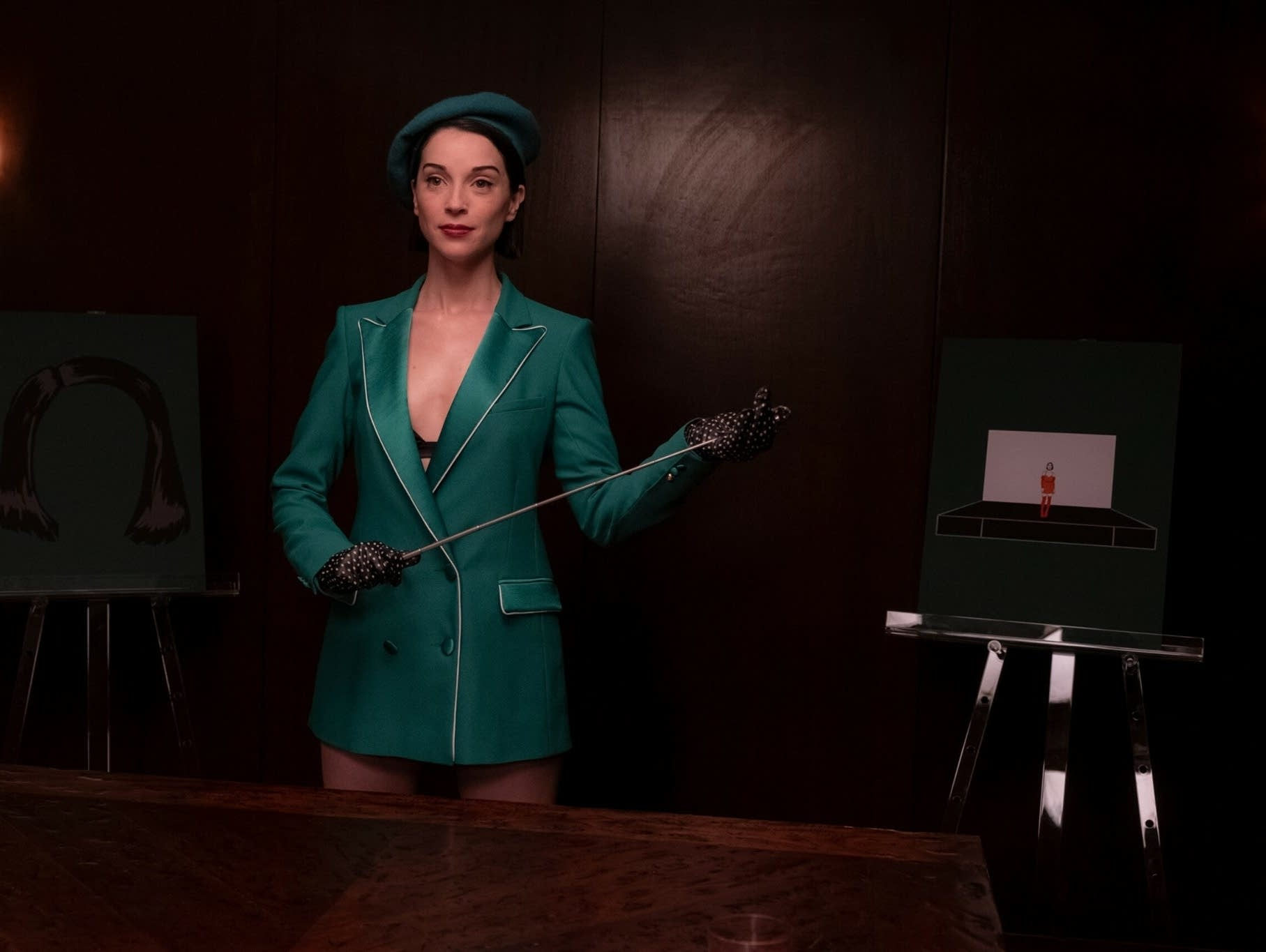 St. Vincent standing in green suit holding pointer.