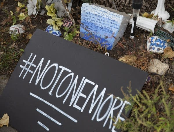 """A sign that reads """"#notonemore"""" sits in front of painted rocks."""
