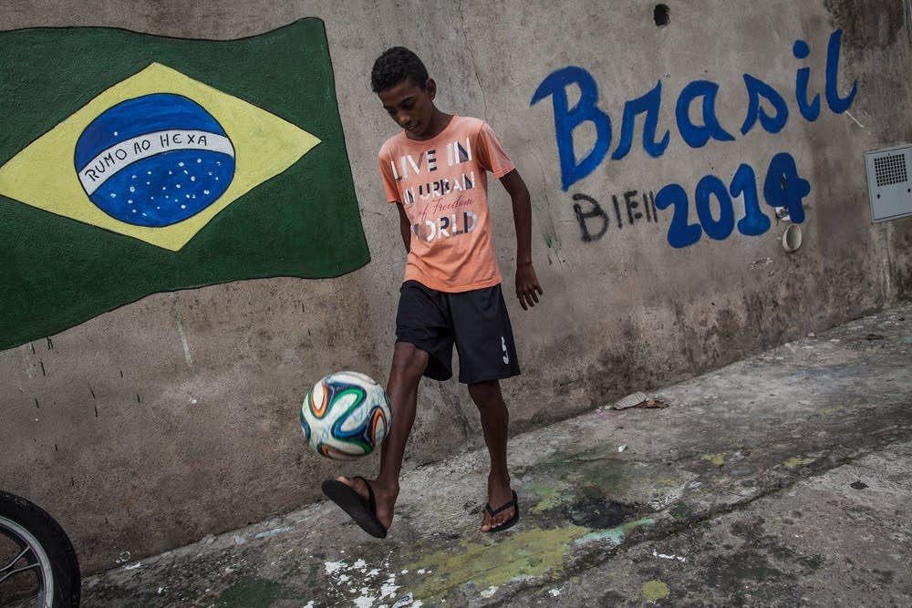 A boy plays soccer in the streets