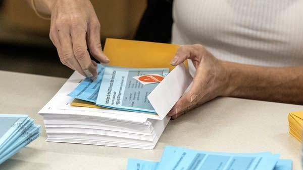 A pair of hands prepares a mail-in ballot.