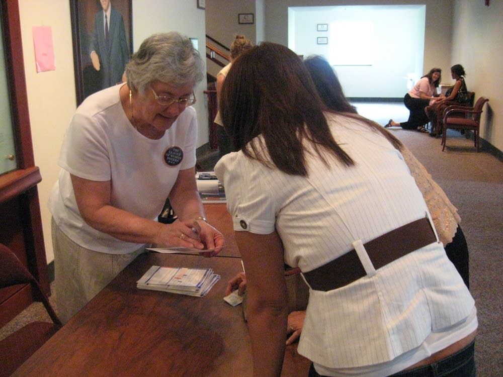 Judy Stuthman helps register a new voter