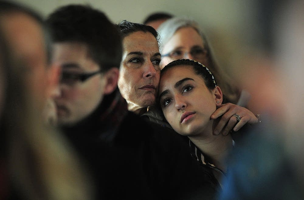 A mother and daughter attend a prayer service
