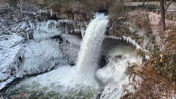 A few of the waterfall surrounded with ice and a river below