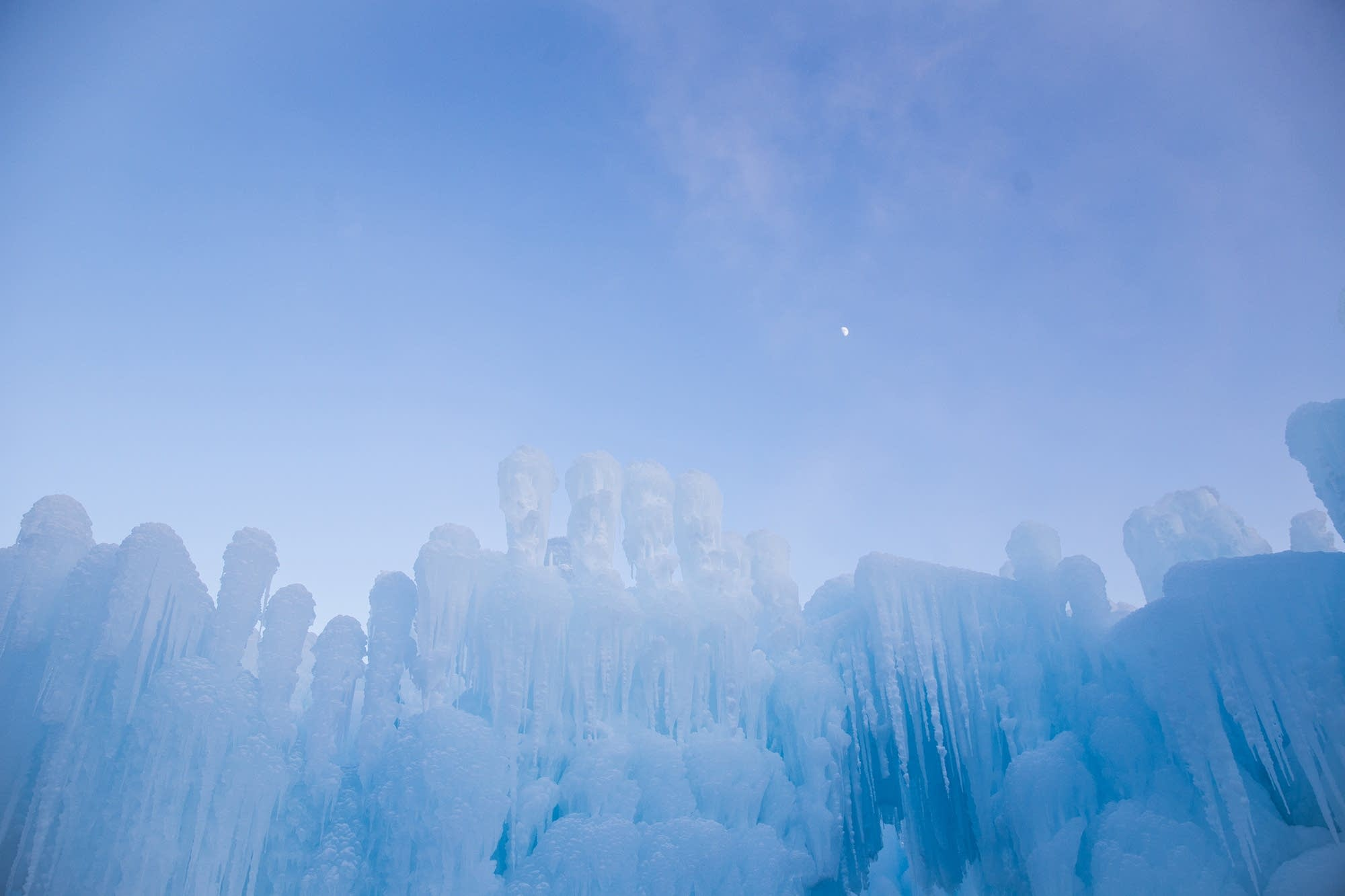 The moon rises above Ice Castle walls.