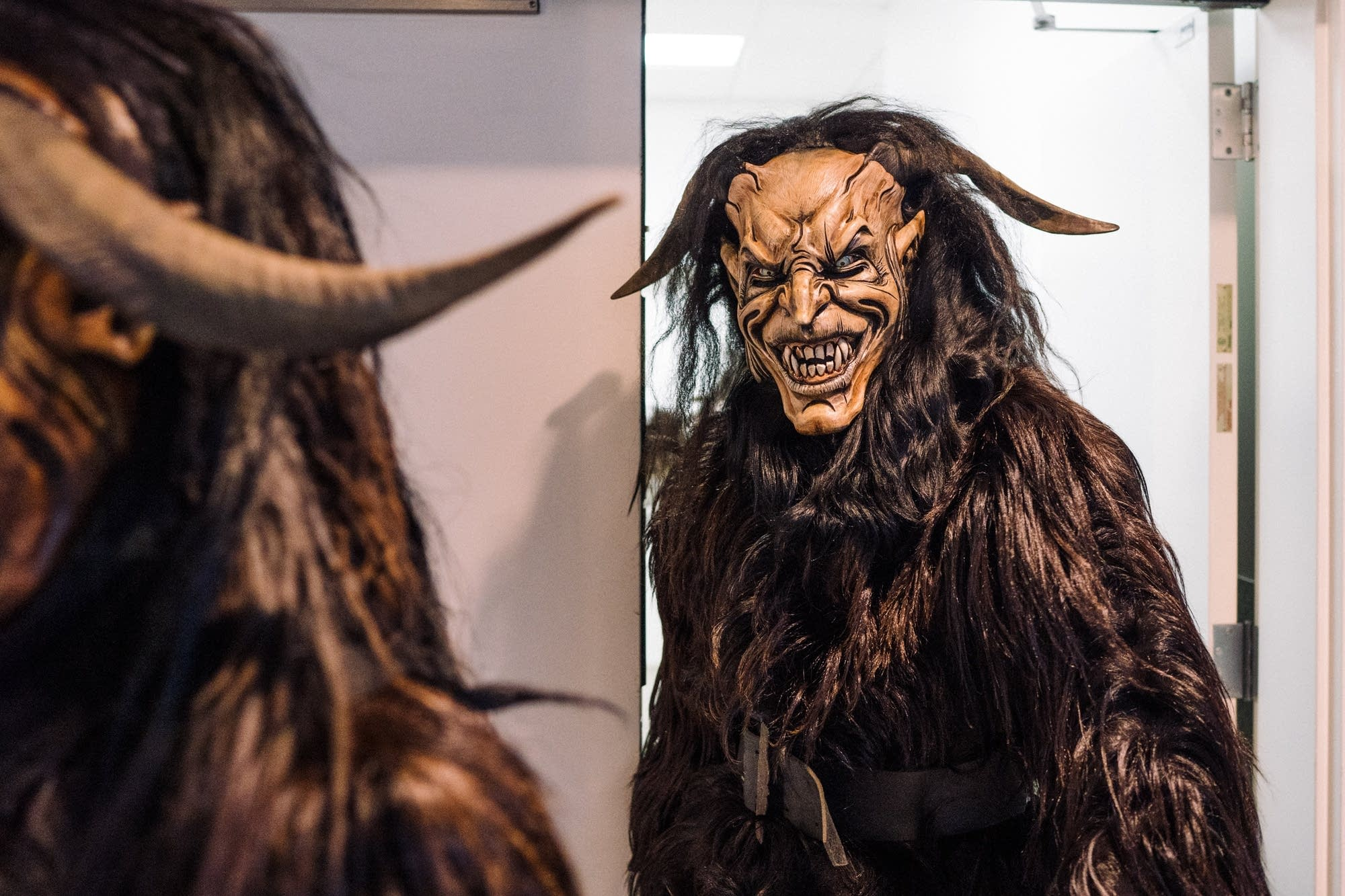 Multiple Krampus leave the hallway where they dressed.