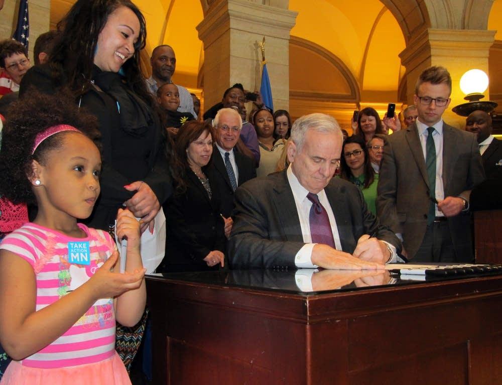Dayton signs minimum wage increase into law.