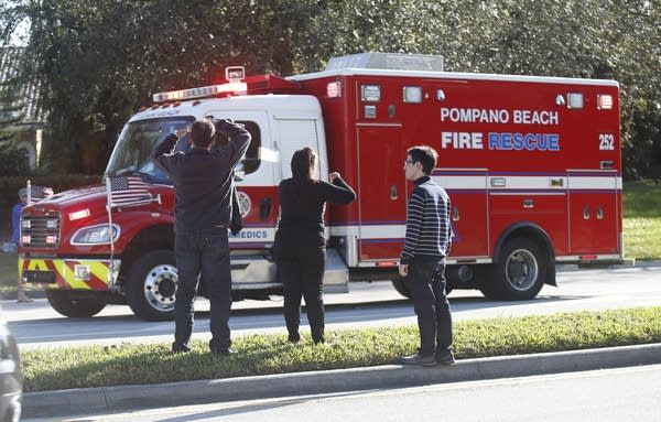 Anxious family members watch a rescue vehicle pass by.