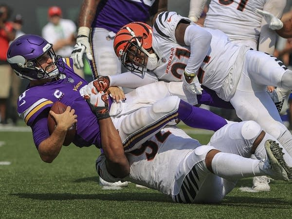 Two football players sack a quarterback