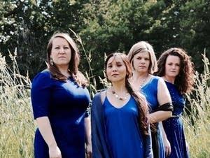 Four women dressed in blue