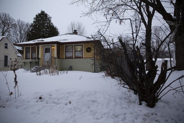 A one-story yellow house on a snowy yard.