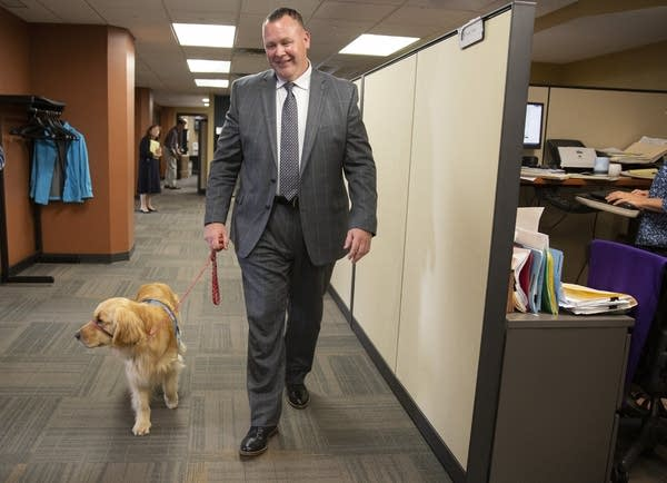 Bill Kube, a victim/witness advocate, walks with Norie in the office.