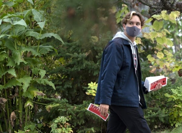 A teenager holding pamphlets and walking in a neighborhood.