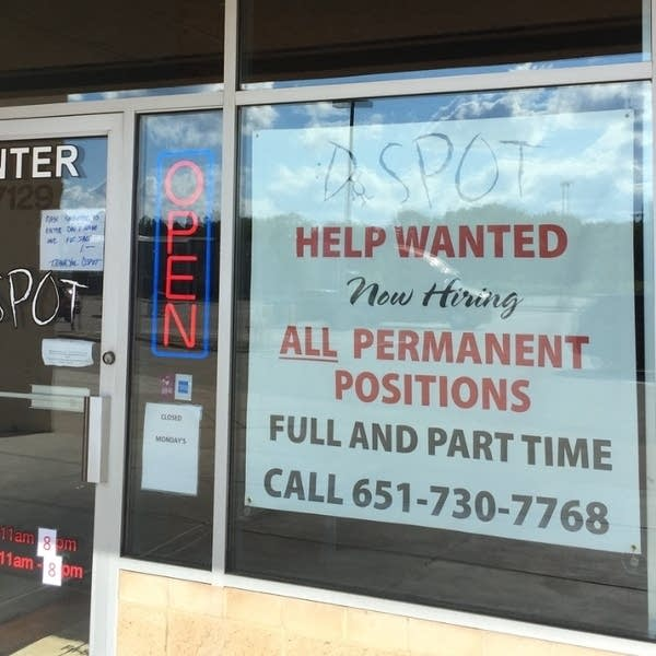 A sign reading 'help wanted' is taped to a storefront window.