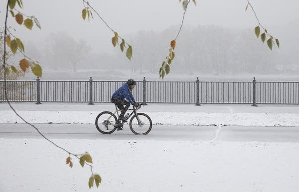 A person rides a bike on a snowy bike path.