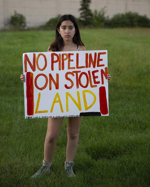 A teenage girl holds a sign that reads No pipeline on stolen land