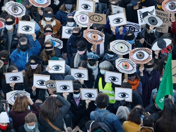 Protesters holds placards depicting eyes