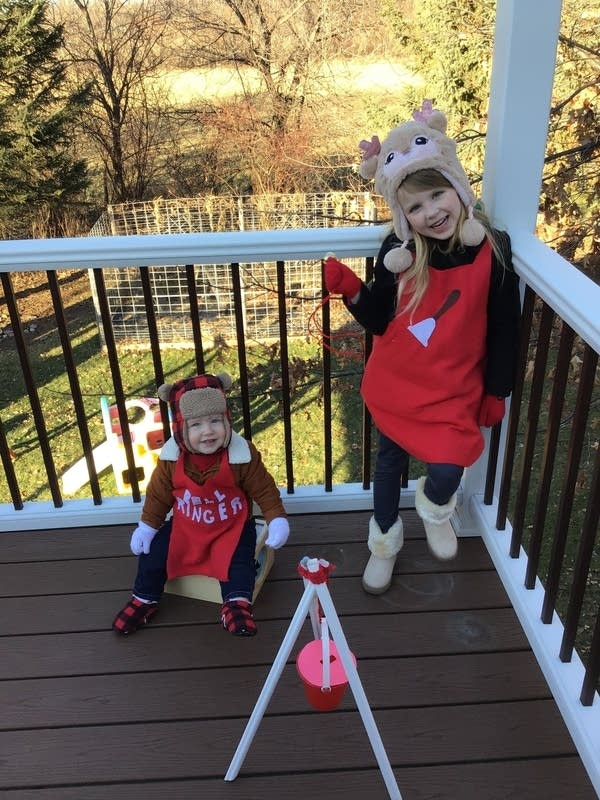 Two children wearing red aprons.