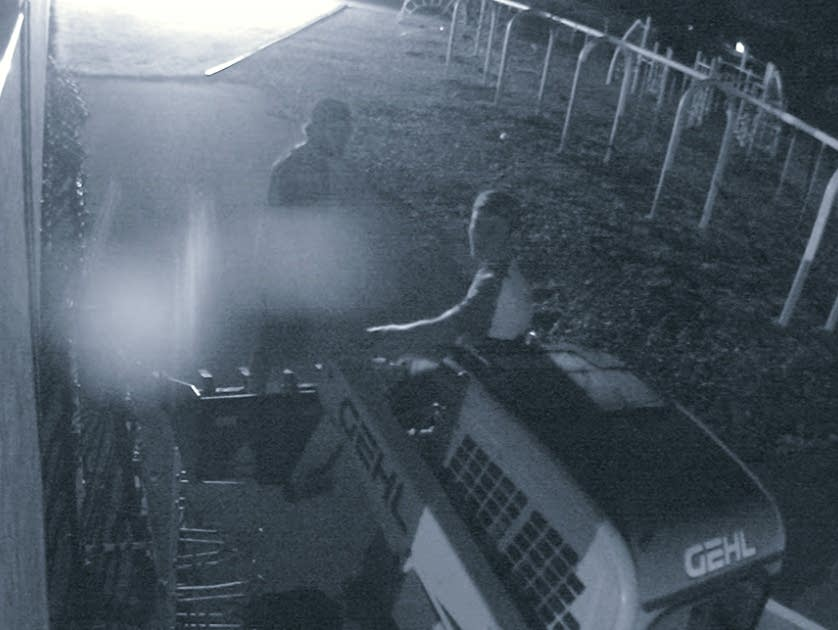 Surveillance image of two suspects stealing a skid loader.