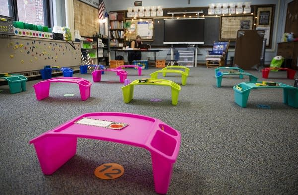 Lap trays are place apart from each other on a classroom floor.
